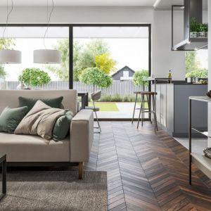 Na uwagę zasługuje ciemna, drewniana podłoga, ocieplająca jasne wnętrze. Fot. HomeKONCEPT