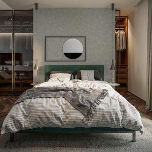 Za łóżkiem w sypialni zaprojektowano komfortową garderobę. Fot. HomeKONCEPT