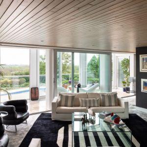 """Duże przeszklenia świetnie """"doświetlają"""" wnętrze salonu światłem naturalnym. Fot. Stiff + Trevillon"""