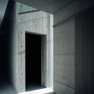 Część parteru, z garażem i wejściem, wykonano z betonu, w którym pozostawiono widoczne otwory po śrubach szalunkowych. Fot. FujiwaraMuro Architects