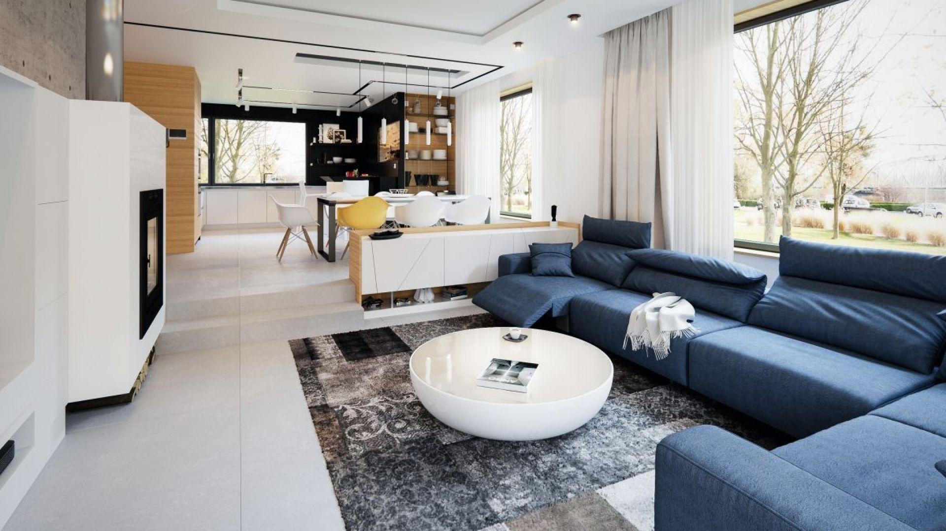 Centralne miejsce w salonie zajmują meble wypoczynkowe w modnym granatowym odcieniu. Fot. Archetyp