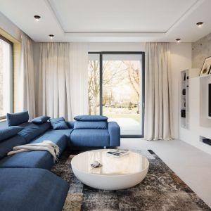 Wyjątkową ozdobą wnętrza jest ściana telewizyjno-kominkowa. Biała zabudowa meblowa i zabudowa kominka pięknie prezentują się na tle betonowych płyt. Fot. Archetyp