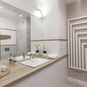 Obszerna szafka pod umywalką, a obok niej sięgający sufitu słupek na  pralkę, kosz na bieliznę i proszki do prania. Wszystko więc można schować, a na wierzchu (na narożnej półce) pozostawić tylko estetyczne rzeczy. Fot. Pracownia MGN