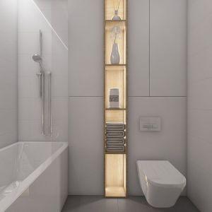 Zabudowana wnęka na sedesem jest niewidoczna, bo zlewa się z tłem ścian. W oczy rzuca się natomiast słupek z podświetlanymi półkami - wielka ozdoba tej łazienki. Fot. Pracownia MGN