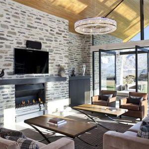 Salon doskonale odzwierciedla połączenie tradycji i nowoczesności. Kamienna ściana, drewniany strop i wygodne fotele świetnie pasują do dużych przeszkleń i nowoczesnego kominka. Fot. M&W