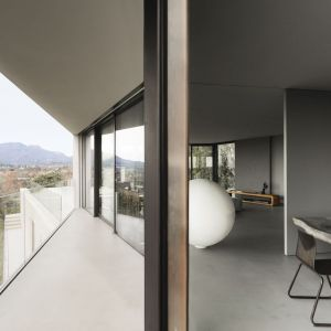 W pomieszczeniach królują naturalne materiały, takie jak kamień i drewno, a dodatkowe duże przeszklenia pozwalają poczuć jeszcze większą więź z otaczającym krajobrazem. Fot. Simone Bossi