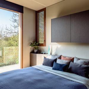 """Duże okno w sypialni """"otwiera"""" wnętrze na zielony ogród. Fot. The Modern House"""
