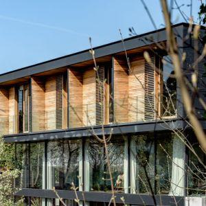Drewniane osłony okienne ocieplają nowoczesną bryłę budynku. Fot. The Modern House