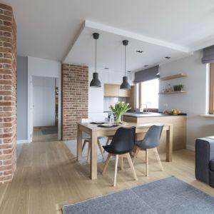 Wyraźny podział na strefy zaznacza w tym mieszkaniu zróżnicowana podłoga oraz podwieszony nad kuchnią sufit, w którym zainstalowano spoty, dające dobre światło do pracy. Z dolną zabudową w kształcie litery U zintegrowano stół. Jego blat oświetlają dwie lampy wiszące.