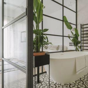 W sypialni zdecydowano się umieścić przeszkloną łazienkę z białą wanną i wzorzystymi cementowymi kaflami podłogowymi Purpura. Fot. Studio.O