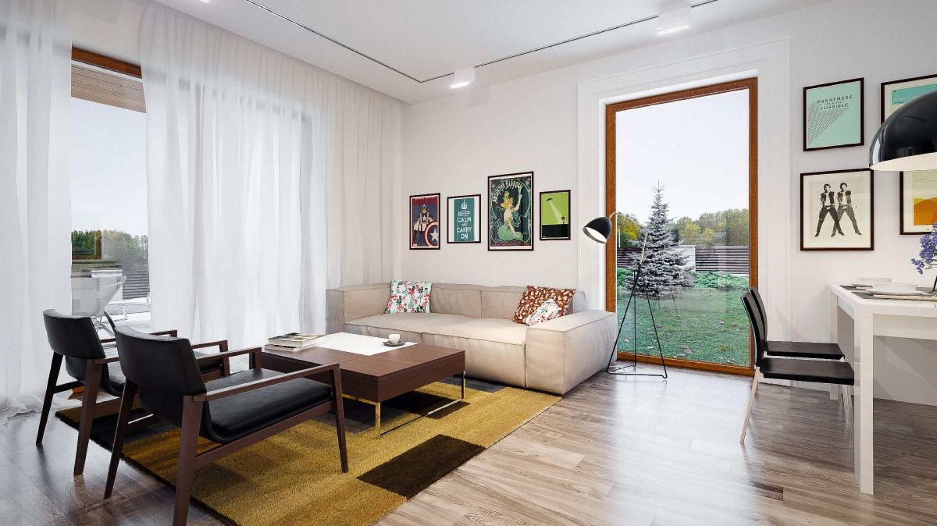 Salon urządzony jest z dużym smakiem. Białe ściany dobrze komponują się z naturalnym drewnem na podłodze. Całość zdobią modne, kolorowe grafiki i nowoczesne meble. Fot. Archetyp