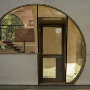 Nietypowy kształt wnętrz domu można już odkryć przy samym wejściu i na ganku. Tam zauważymy pierwsze okrągłe przeszklenia, które zostały celowo wkomponowane nie tylko w fasadę rezydencji, ale też i dach. Fot. Paul Warchol