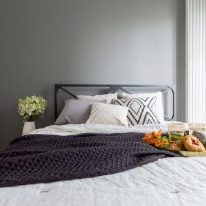 Sypialnia zdecydowanie nawiązuje do surowego klimatu industrialnego – szara ściana i metalowa rama łóżka korespondują z resztą wnętrza, jednocześnie nadając tej części mieszkania bardziej klasyczny, industrialny ton. Fot. Decoroom