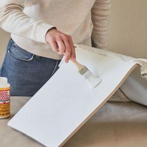 Nałóż sporą ilość kleju do decoupage'u lub kleju Mod Podge na powierzchnię krzesła. Małymi fragmentami wygładź tkaninę ułożoną na pokrytej klejem powierzchni. Fot. Bosch
