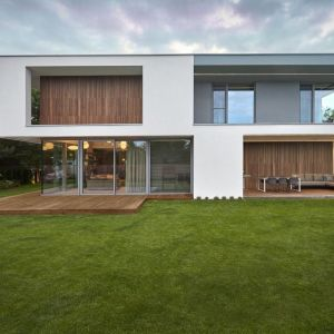 Dom składa się z dwóch brył – białej, dla której charakterystyczne są płaskie elewacje, obłożone elementami drewna oraz szarej, cofniętej względem białej. Fot. 81.waw.pl