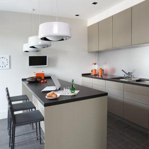 Kuchnia została utrzymana w ascetycznym, minimalistycznym stylu. Prosta zabudowa i wyspa kuchenna tworzą tło dla dodatków w radosnym odcieniu pomarańczy. Fot. Aneta Tryczyńska
