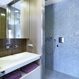 Łazienka ma nowoczesny charakter. Prysznic wykończono płytkami przypominającymi rybią łuskę w przyjemnym, błękitnym odcieniu, a ścianę za umywalkami pokryto drewnem. Fot. Aneta Tryczyńska