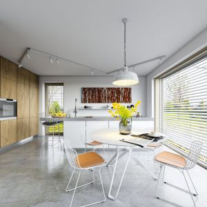 Ogromne przeszklenia prowadzą z jadalni wprost na taras, który jest naturalnym przedłużeniem salonu na letnie dni. Fot. Domy z Wizją