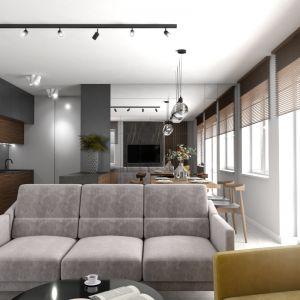 Zabudowa kuchenna z trzech rodzajów płyt: fornirowanej drewnem orzecha, lakierowanej na szaro oraz na biało, ma salonowy charakter, dzięki czemu idealnie komponuje się z resztą wystroju otwartej strefy dziennej. W lustrze, którym wyłożono ścianę za jadalnią, odbijają się fragmenty aranżacji, co wywołuje wrażenie większej przestronności wnętrza. Fot. Pracownia Architektoniczna MGN
