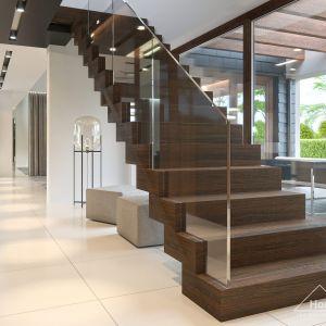 Drewniane schody ze szklaną balustradą dobrze pasują do stylu wnętrza. Fot. HomeKONCEPT