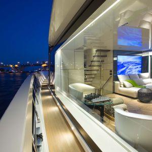Jacht San Lorenzo uosabia nowoczesną definicję piękna, w którym innowacja spotyka się z kultowym designem. Designerskie meble w jasnej kolorystyce skłaniają do wypoczynku. Biel kontrastuje tu z drewnem w ciemnych odcieniach.Fot. Forestile