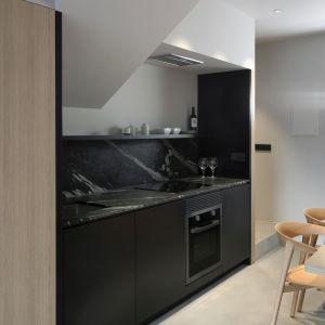 Możemy znaleźć w niej kuchnię, łazienkę dla gości oraz schody. Również przeciwległa ściana została pokryta drewnem, gdzie dodatkowo umieszczono telewizor i garderobę. Fot. Ritmonio