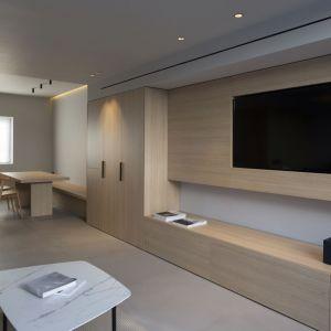 Również przeciwległa ściana została pokryta drewnem, gdzie dodatkowo umieszczono telewizor i garderobę. W ten sposób ograniczona przestrzeń domu została  w pełni wykorzystana przez architektów. Fot. Ritmonio