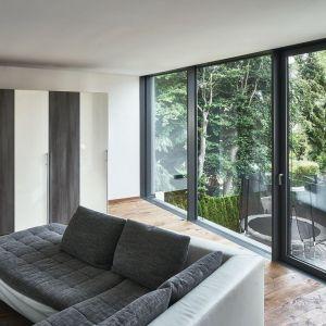 Wielkoformatowe przeszklenia na górnej kondygnacji otwierają salon na widoki ogrodu. Fot. Schüco/Christian Eblenkamp