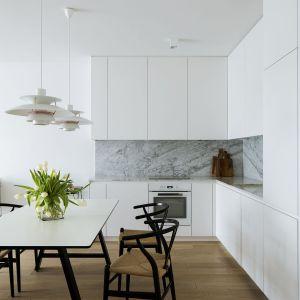 Monochromatyczna zabudowa kuchenna w duecie z marmurem na ścianie nadaje pomieszczeniu klasy. Fot. Madama
