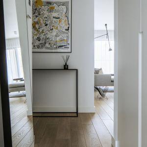 Wizytówkę mieszkania stanowi korytarz – utrzymany w stylistyce, będącej połączeniem klasycznej bieli z drewnem i czarnym dodatkiem w postaci nowoczesnego stolika. Fot. Madama