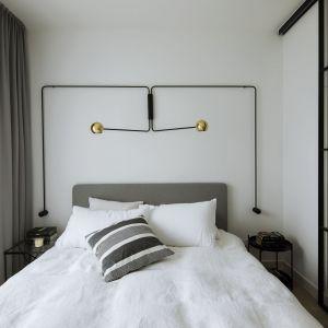Sypialnia stanowi kontynuację minimalistycznego projektu – królują tu proste formy, biele i szarości. Fot. Madama