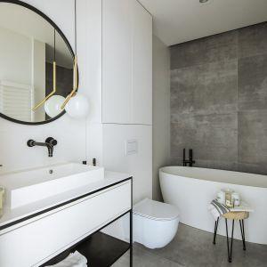 Dominującą biel zestawiono w łazience z powierzchnią imitującą beton – na ścianie oraz podłodze. Fot. Madama
