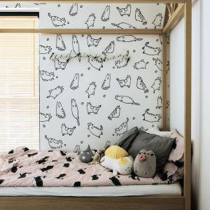 Łóżko, podłoga i stylowe skrzynki na zabawki przełamują monochromatyczne wnętrze. Fot. Madama