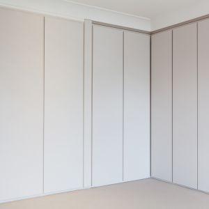 Praktyczne szafy są niemal niezauważalne i nie burzą minimalistycznej aranżacji wnętrza. Fot. Nick Leith-Smith