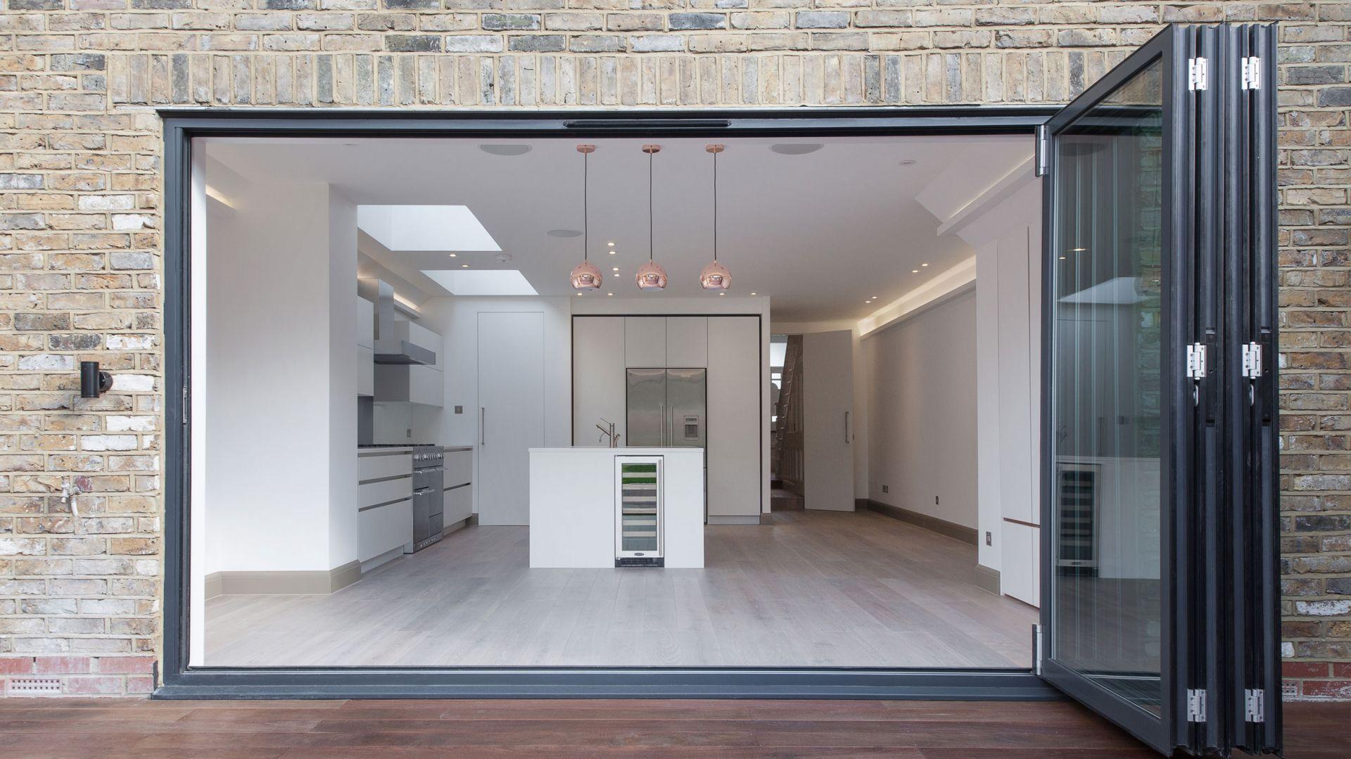 Duże, przeszklone, składane drzwi to idealny sposób na płynne przejście z kuchni do ogrodu. Fot. Nick Leith-Smith
