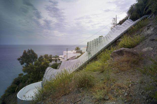 """Rzut oka na dom i uwagę przykuwa oryginalny, pofalowany kształt dachu, który został wykonany z metalu i pokryty powłoką cynkową. Inspiracją przy jego tworzeniu były fale morskie oraz... łuski smocze. Cynkowe płytki """"łuski"""" pokrywają"""