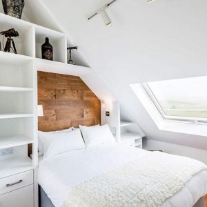 W pięknej białej sypialni ciekawie prezentują się ciemne drewniane elementy, nawiązujące do tradycji budynku. Fot. Evolution Design