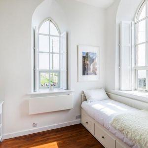 Z jednej z mniejszych sypialni można podziwiać piękny lokalny krajobraz. Gotyckie okna dostarczają też dużo naturalnego światła. Fot. Evolution Design