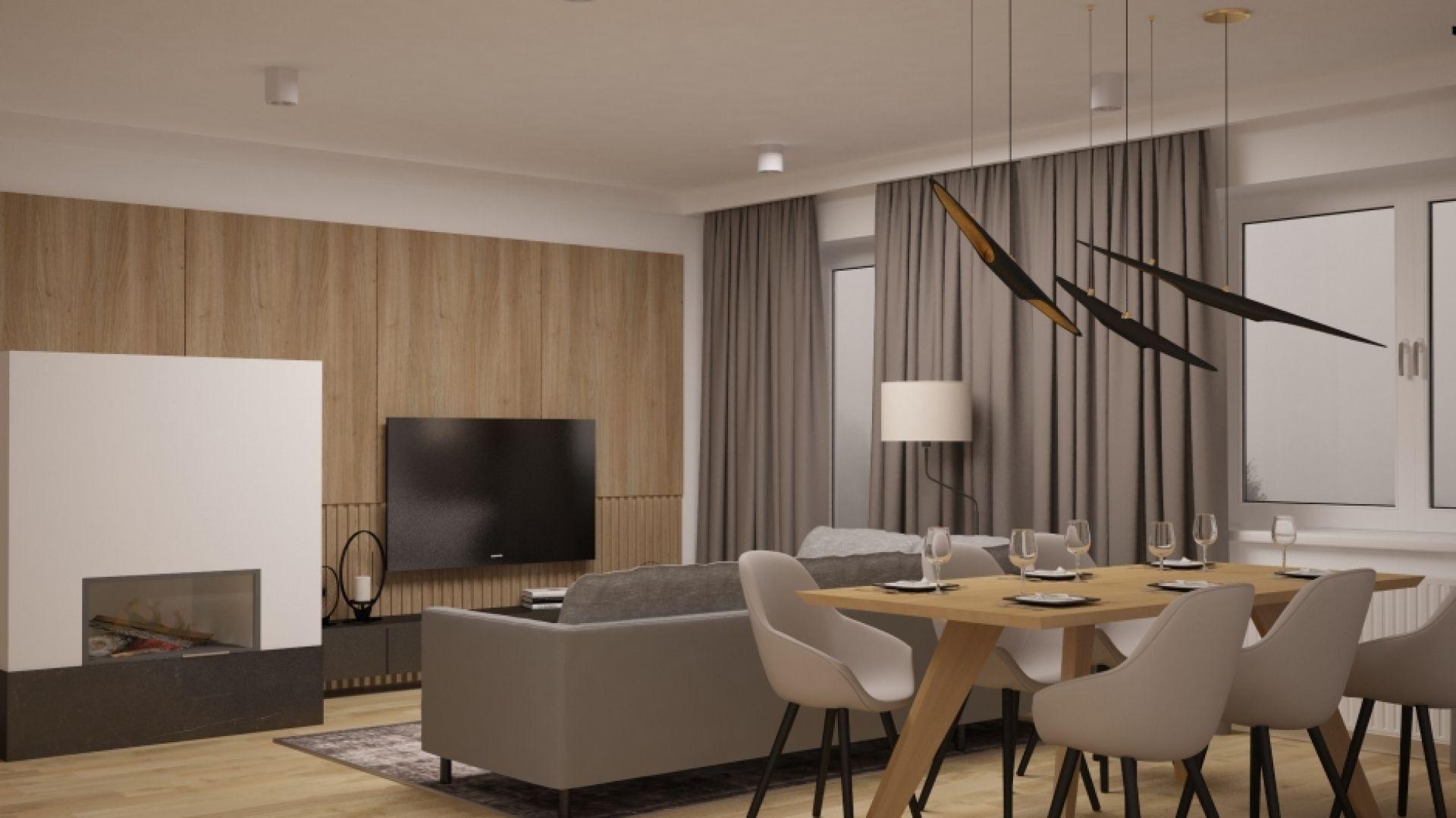 W salonie są sufitowe spoty, na stołem wiszą trzy przypominające ptaki lampy i jest jeszcze taśma LED, zainstalowana w drewnianej okładzinie ściany. Można więc jasno oświetlić całe pomieszczenie albo stworzyć sprzyjający relaksowi nastrojowy półmrok. Fot. Pracownia MGN