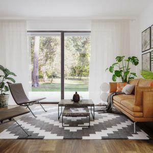Centralne miejsce w salonie zajmuje modna kanapa w beżowym odcieniu.