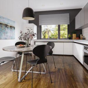 """Kuchnia z zabudową na planie litery """"L"""" to zgrabne połączenie bieli i szarości. Duże okno dodatkowo rozświetla przestrzeń."""