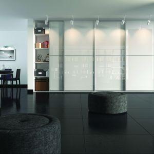 """Białe szkło, zwłaszcza odpowiednio oświetlone gwarantuje wyjątkowe efekty estetyczne. Na zdjęciu: system aluminiowy """"A100"""" z miękkim domykiem, profil """"Calgary"""" anoda naturalna i szkło lacobel. Fot. Indeco"""
