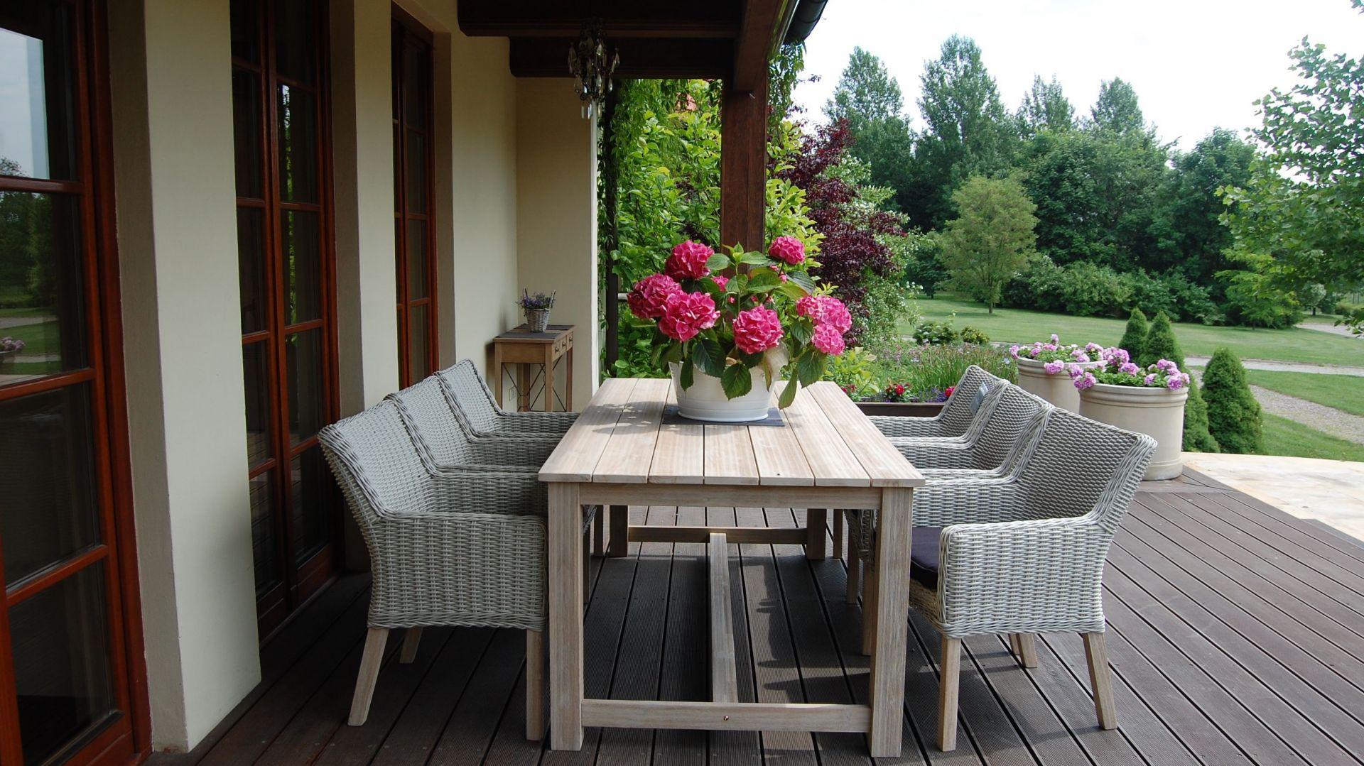 Mura, Miloo to bielone drewno akacjowe, solidny drewniany blat oraz masywne nogi stworzą wyjątkową atmosferę jadalni w środku ogrodu. Fotel Mura, siedzisko wyplatane eco-rattan z drewnianymi nogami.  Fot. House&More