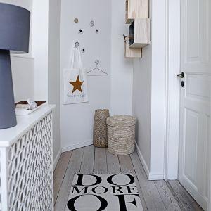 Przedpokój urządzony w stylu skandynawskim - jasna, naturalna podłoga, białe ściany i drzwi, drewniane półki, wyplatane kosze. Dzięki nim korytarz prezentuje się świeżo i przestronnie. Fot. North&South Home