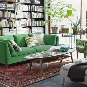 Regał z książkami zajmujący całą jedną ścianę w salonie może być tłem dla wygodnej sofy. Fot. IKEA.