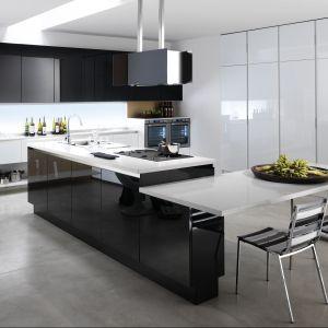 Kuchnia Roma marki Biefbi. Wysoka zabudowa w kolorze białym harmonijnie komponuje się z czarnymi frontami w połysku. Duża wyspa pełni strefę gotowania, połączono ją również z jadalnianym stołem. Fot. Biefbi