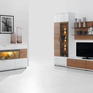 System Corano to połączenie bieli z ciepłem koloru dębu. Dodatkowo w przeszklonych segmentach zastosowano ciepłe oświetlenie, które idealnie komponuje się z drewnianymi elementami, tworząc w pomieszczeniu ciepły i klimatyczny nastrój. Fot. Bydgoskie Meble