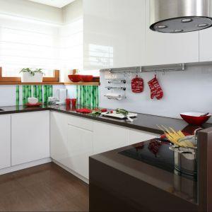 Chłodną tonację białej kuchni można w prosty sposób przełamać dodatkami w soczystych kolorach. Dekoracja ścienna z motywem zieleni oraz czerwone dodatki tworzą razem bardzo zgraną kompozycję. Projekt: Katarzyna Mikulska-Sękalska. Fot. Bartosz Jarosz