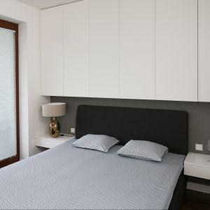 Dzięki wysokim szafkom, umieszczonym nad łóżkiem możemy sprawić, że mała sypialnia małżeńska będzie wydawała się wyższa. Projekt: Agnieszka Ludwinowska. Fot. Bartosz Jarosz