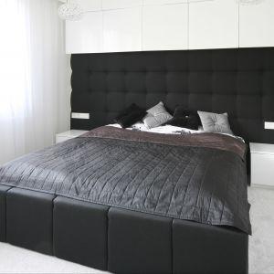 Sypialnia urządzona w czerni i bieli. Piękny dekoracyjny zagłówek rozciągnięty na całą szerokość ściany to ciekawy element wnętrza. Projekt. Dominik Respondek Fot. Bartosz Jarosz